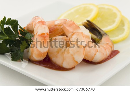 Shrimp cocktail with sauce, lemon slices, and parsley. - stock photo