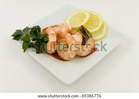 Shrimp cocktail with sauce, lemon slices and parsley on a plate - stock photo