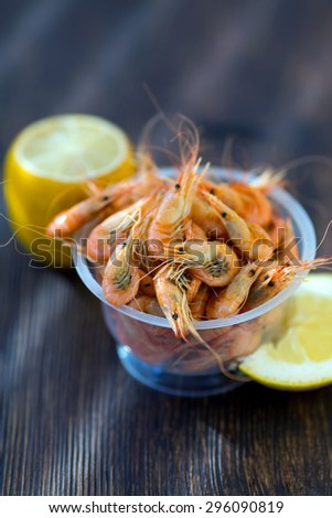 Shrimp from the Black Sea. Snack to beer and wine. Serve cooked shrimp and lemon on a bar table. Delicious fresh cooked shrimp prepared to eat. Cooked shrimps with lemon on wooden table. - stock photo