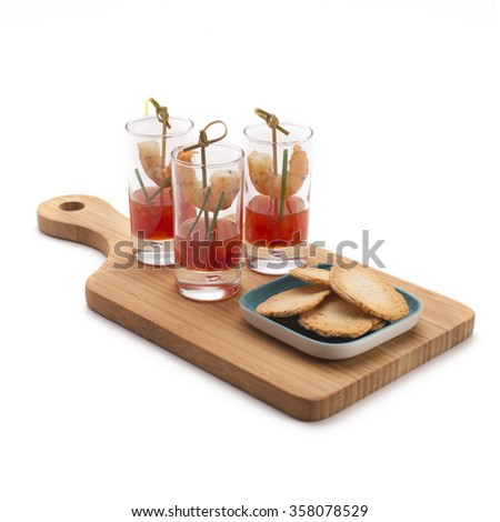 Shrimp in shot glasses with sweet and chili red sauce served on a wooden board with  crackers isolated on white. Party food. - stock photo