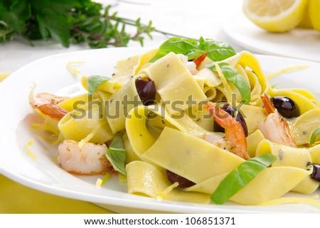 Shrimp lemon pepper Pappardelle pasta with fresh basil, and black olives. - stock photo