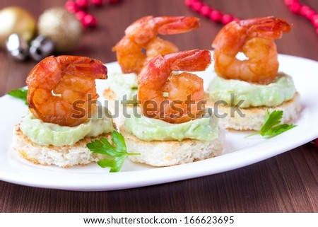 Shrimp on toast with guacamole sauce avocado, Christmas tasty elegant appetizer, starter for new year party - stock photo