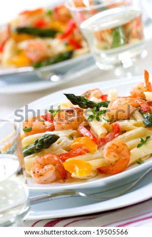 Shrimp Penne (tube-shaped pasta) with asparagus, bell pepper, origan and creamy Alfredo sauce . Shallow DOF - stock photo