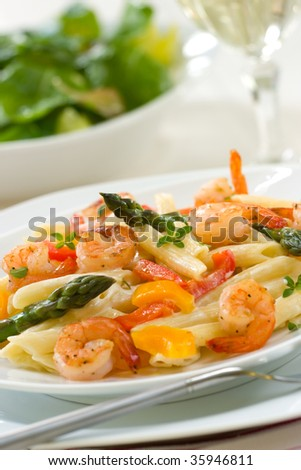 Shrimp Penne (tube-shaped pasta) with asparagus, bell pepper, origan and creamy Alfredo sauce . Green salad. Shallow DOF - stock photo