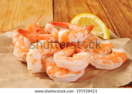 Shrimp prawns on butcher paper with a wedge of lemon - stock photo