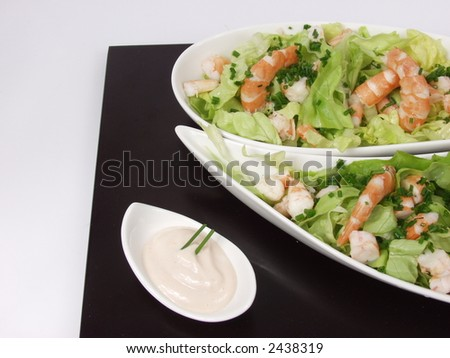 shrimp salad in a white exclusives plates with sauce