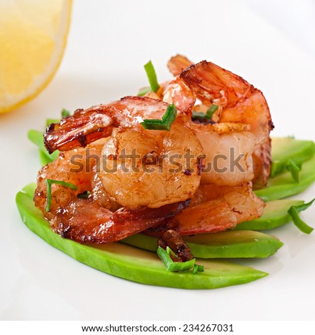 Shrimp sauteed with garlic and soy sauce on a cushion of avocado slices - stock photo