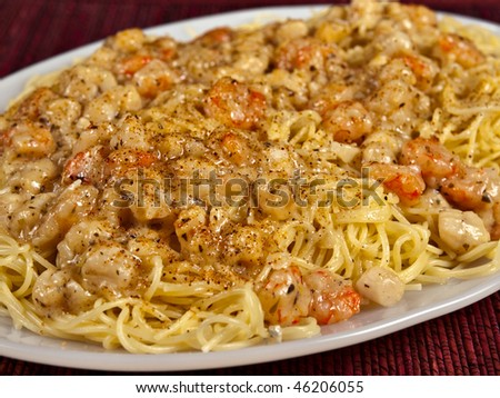 Shrimp Scampi over a plate of Angle Hair pasta - stock photo
