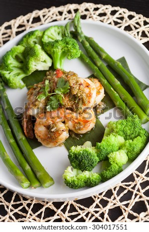 Shrimp scampi seafood dish with broccoli and asparagus.  Shallow depth of field. - stock photo