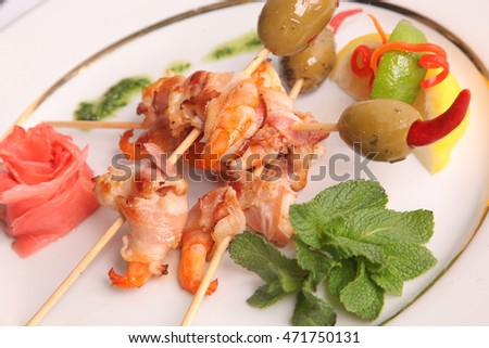 shrimp skewers with olives on plate