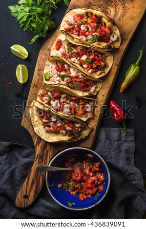 Shrimp tacos with homemade salsa, limes and parsley on wooden board over dark background. Top view. Mexican cuisine - stock photo