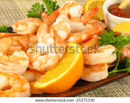 Shrimp with cocktail sauce, lemon wedges, and parsley.