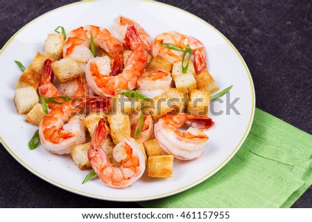 Shrimp with crispy croutons and scallions in white plate