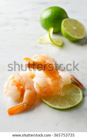 Shrimp with lime on a marble table. Raw ingredients - stock photo