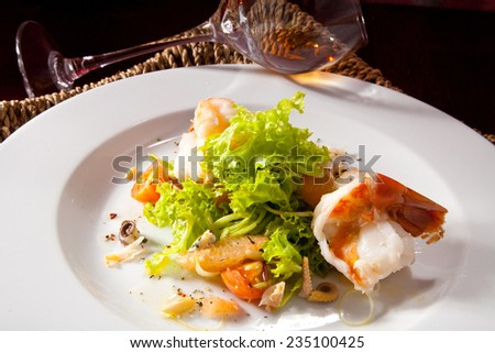 Shrimp with Octopus in the Leaves of Green Salad with Cherry Tomatoes and Fresh Herbs. Photo, picture - stock photo