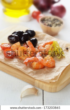 Shrimps and olives on cut board