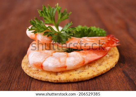 Shrimps and parsley saltine cracker snack - stock photo