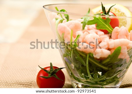 shrimps cocktail appetizer on brown towel with lemon and cherry tomatoes - stock photo
