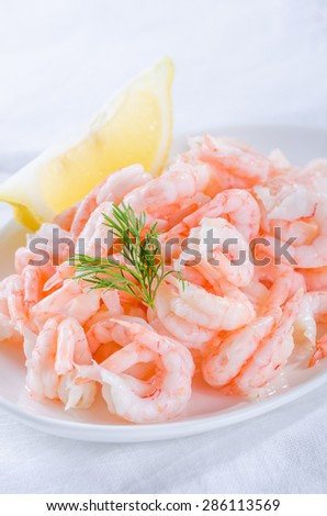 shrimps - cooked and peeled with lemon wedge on white - stock photo