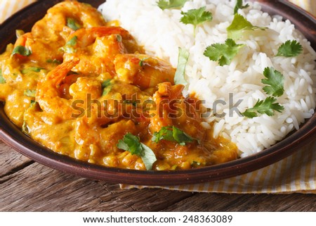 Shrimps in curry sauce with rice and cilantro closeup on a plate. horizontal  - stock photo