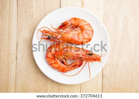 Shrimps on white dish over wood table - stock photo