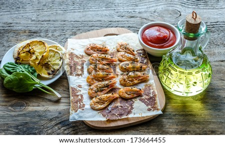 Shrimps with lemon and spicy sauce on the wooden background - stock photo