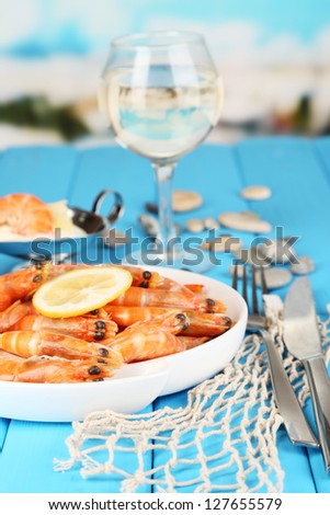 Shrimps with lemon on plate on wooden table on blue natural background