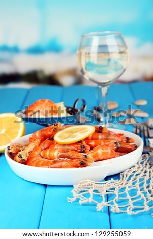 Shrimps with lemon on plate on wooden table on blue natural background - stock photo
