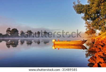 Shrouded by mist a secured boat on the Bellinger River at dawn - stock photo