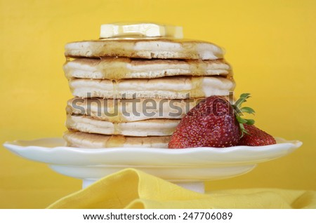 Shrove Pancake Tuesday stack of pancakes with honey and butter on yellow and aqua blue vintage shabby chic table, closeup. - stock photo