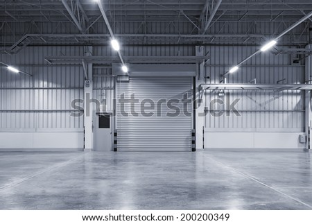 Shutter door inside factory, night scene. (blue color tone) - stock photo
