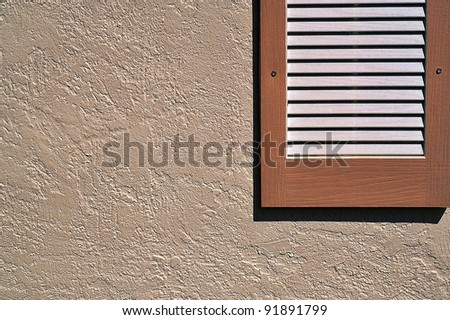 Shutter on exterior stucco wall - stock photo