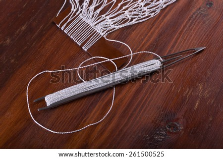 Shuttle for tying fishing nets at home - stock photo