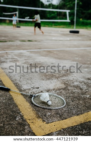 Shuttlecock and badminton racket on the cement floor