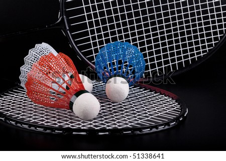 Shuttlecock and badminton racket over black background