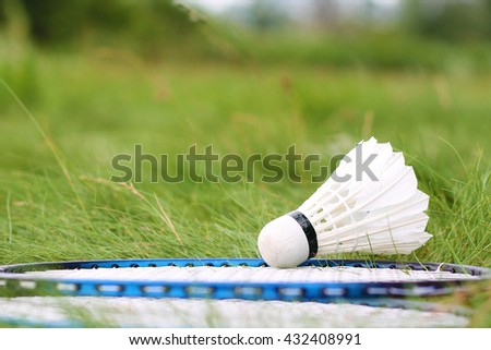 Shuttlecock and rackets for badminton on the green grass. Summer game for healthy lifestyle. - stock photo