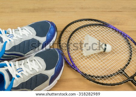 Shuttlecock on badminton racket and  shoe on wooden background,select focus