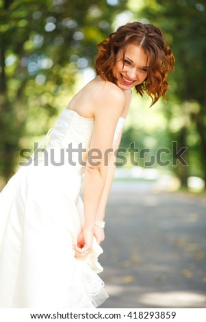 Shy and smiling - bride looks down at the ground while she poses in the park - stock photo