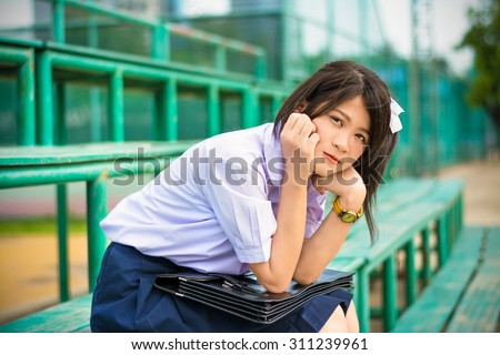 Shy Asian Thai schoolgirl student in high school uniform education fashion is sitting on a metal stand and showing facial bashful expression - stock photo