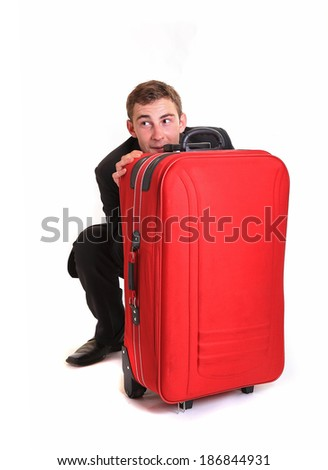 Shy business man hide behind red luggage - stock photo