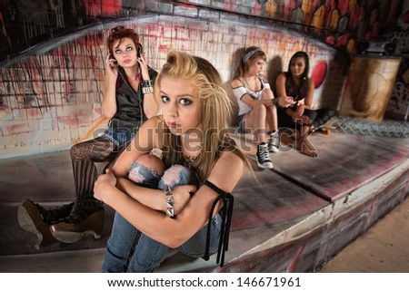 Shy Caucasian teenager sitting with group of young ladies - stock photo