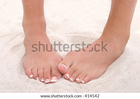 Shy Feet With Pedicure Standing in Sand.