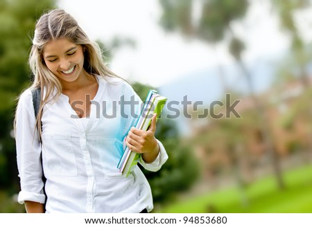 Shy female student walking outdoors and smiling - stock photo