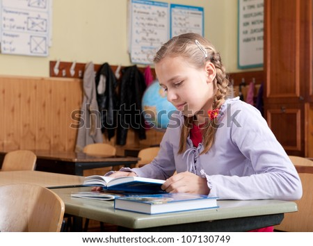 Shy girl reading book in classroom at school