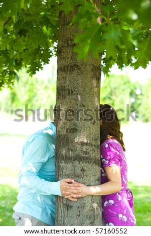 Shy kiss behind a tree - stock photo