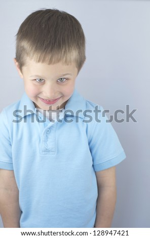 Shy little boy smiling with his head down,isolated. - stock photo