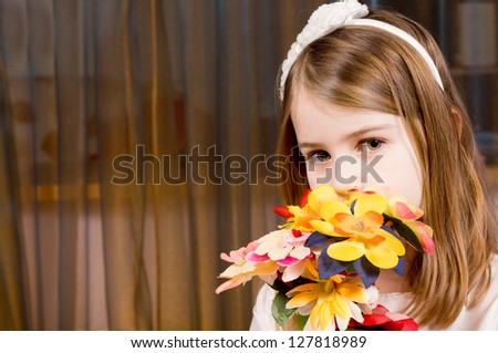 Shy pretty little blonde girl with a bouquet of flowers holding them in front of the face as she looks at the camera against a curtain backdrop with copyspace - stock photo