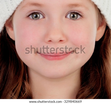 Shy pretty little girl with wool cap smiling - stock photo