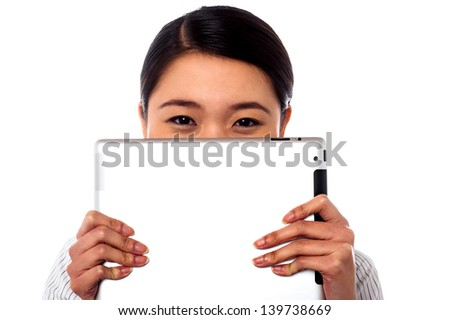 Shy smiling asian woman hiding her face with tablet pc