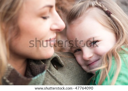 Shy smiling little girl on mother's hands, shallow DOF, focus on daughter - stock photo
